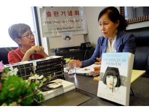 "Author Maija Rhee Devine, right, speaks about her book ""The Voices of Heaven"" as Brenda Paik Sunno listens during a book reading and signing at Seoul Selection Publishing in Irvine on Sunday. ""The Voices of Heaven"" is a love story set during the Korean War."